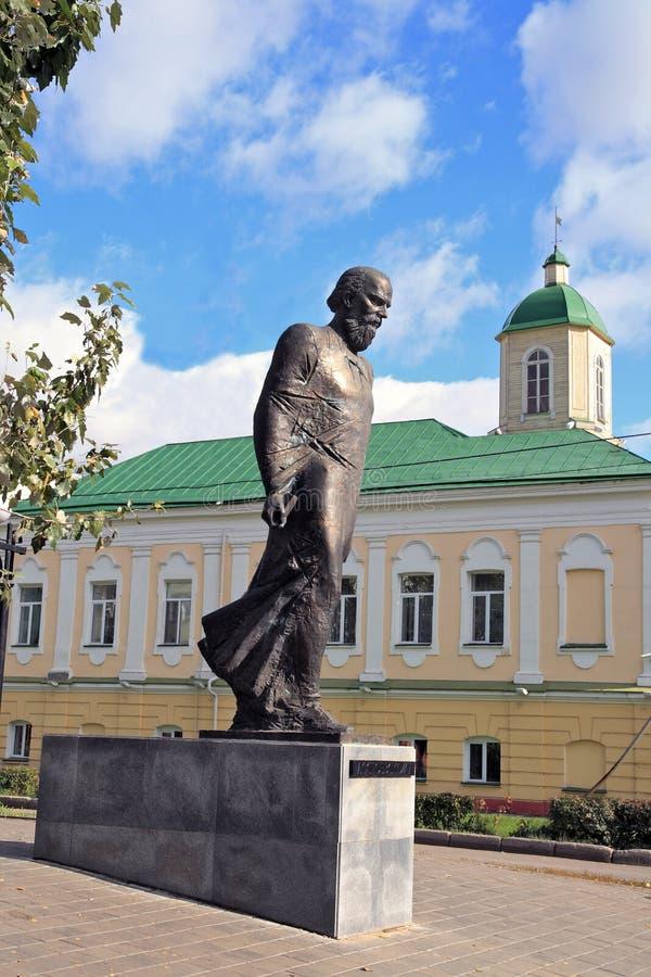 Μνημείο στο ρωσικό συγγραφέα Dostoevsky στο Ομσκ ενάντια στο σκηνικό της οικοδόμησης του guardhouse του 18ου στοκ φωτογραφία με δικαίωμα ελεύθερης χρήσης