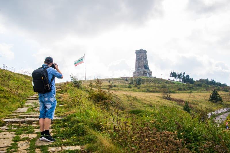 Μνημείο Shipka με μια βουλγαρική σημαία και έναν φωτογράφο, τουρίστας στοκ φωτογραφία με δικαίωμα ελεύθερης χρήσης