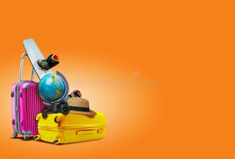 Μοβ και κίτρινες βαλίτσες σε πορτοκαλί φόντο Υπάρχει μια υδρόγειος, μια σανίδα, ένα καπέλο και μια κάμερα πάνω τους στοκ φωτογραφία