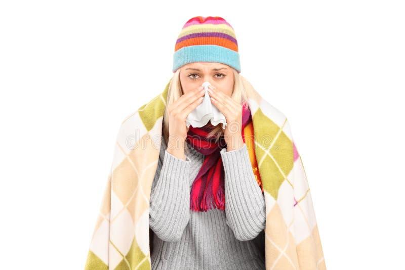 Μολυσμένη γυναίκα που καλύπτεται με το κάλυμμα που φυσά τη μύτη της στον ιστό   στοκ φωτογραφίες
