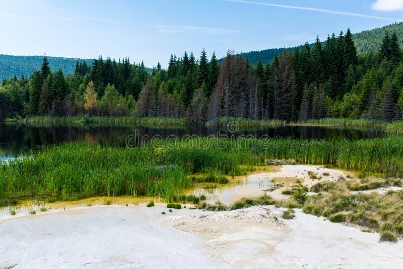 Μολυσμένη λίμνη με τον καολίνη στο εγκαταλειμμένο λατομείο με τον όμορφο μπλε ουρανό στοκ φωτογραφίες