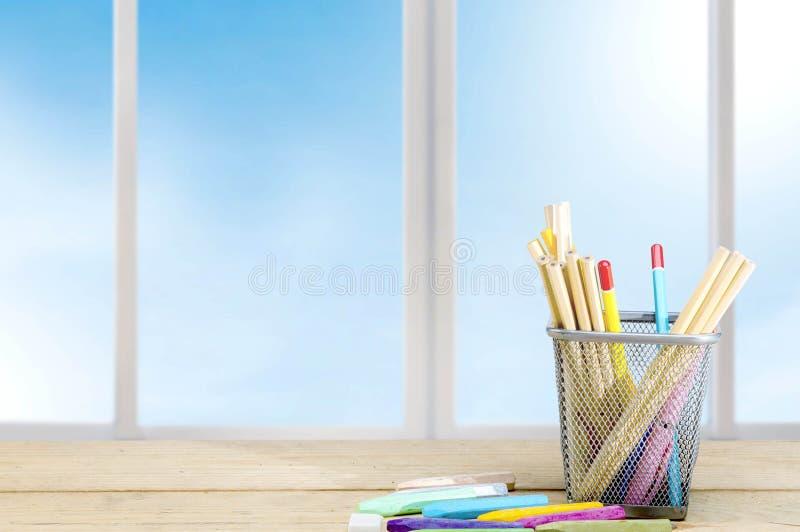 Μολύβια στο εμπορευματοκιβώτιο καλαθιών και ζωηρόχρωμα κραγιόνια στον ξύλινο πίνακα στοκ εικόνα με δικαίωμα ελεύθερης χρήσης