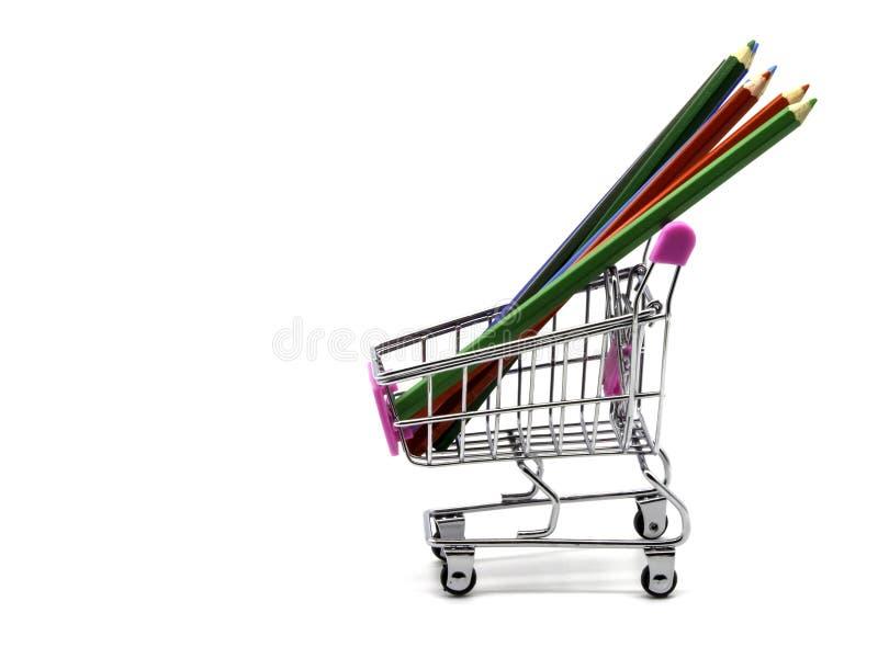 Μολύβια χρώματος και κάρρο αγορών που απομονώνονται και άσπρο υπόβαθρο στοκ εικόνα