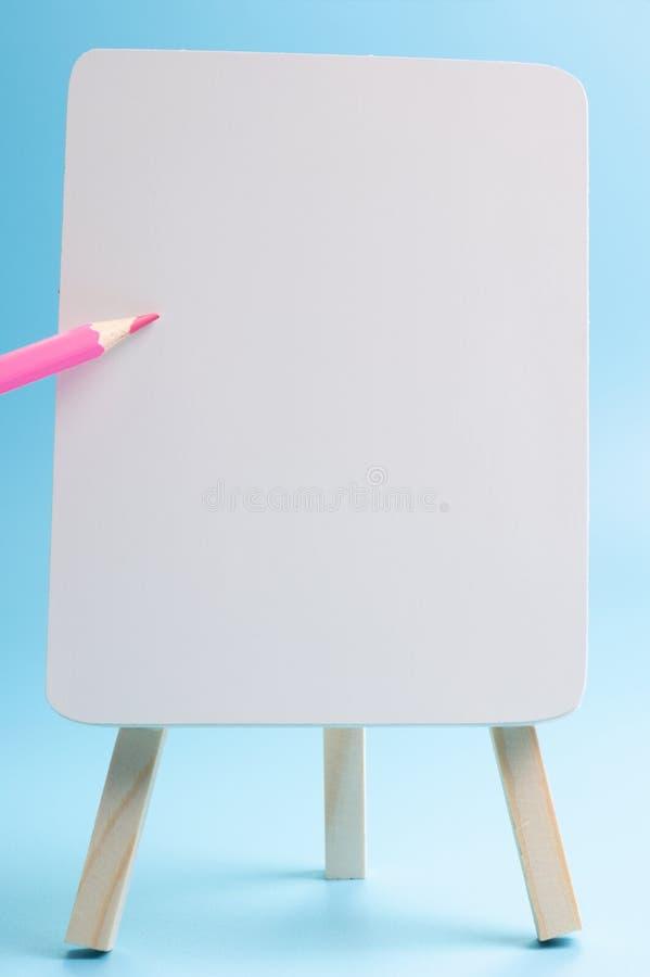 Μολύβι κόκκινου χρώματος που επιπλέει το άσπρο easel μπροστινό μπλε υπόβαθρο στοκ εικόνες με δικαίωμα ελεύθερης χρήσης