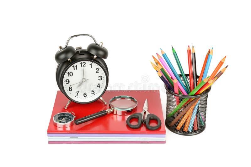 Μολύβι, χαρτικά, βιβλίο, ξυπνητήρι και άλλες σχολικές προμήθειες στοκ εικόνες