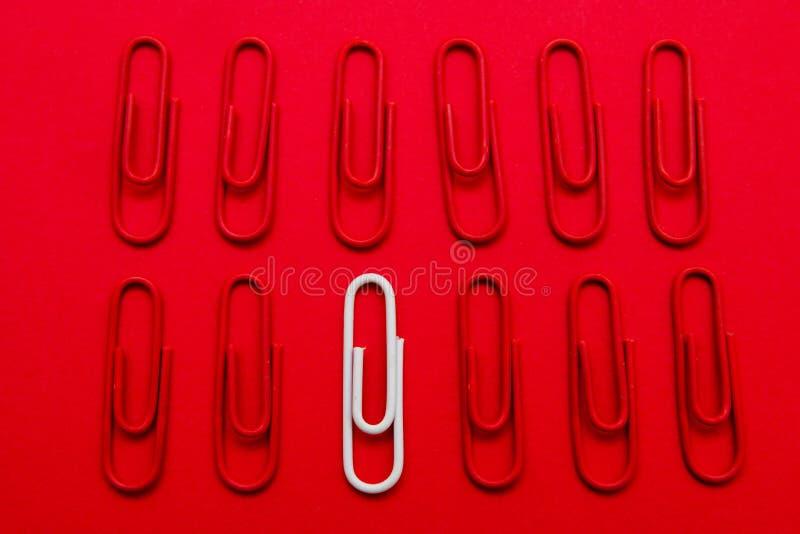 Μοναδική ιδέα έννοιας συνδετήρων της Λευκής Βίβλου σχετικά με το κόκκινο υπόβαθρο, στάση έξω από το πλήθος στοκ φωτογραφίες