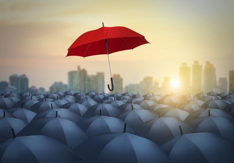 Μοναδική κόκκινη ομπρέλα μεταξύ των μαύρων ομπρελών στοκ εικόνες