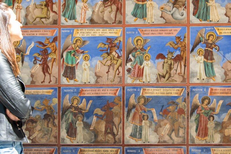 Μοναστήρι Rila, Βουλγαρία Νέο κορίτσι που φαίνεται οι θρησκευτικές νωπογραφίες στις πραγματείες Βίβλων στοκ φωτογραφίες