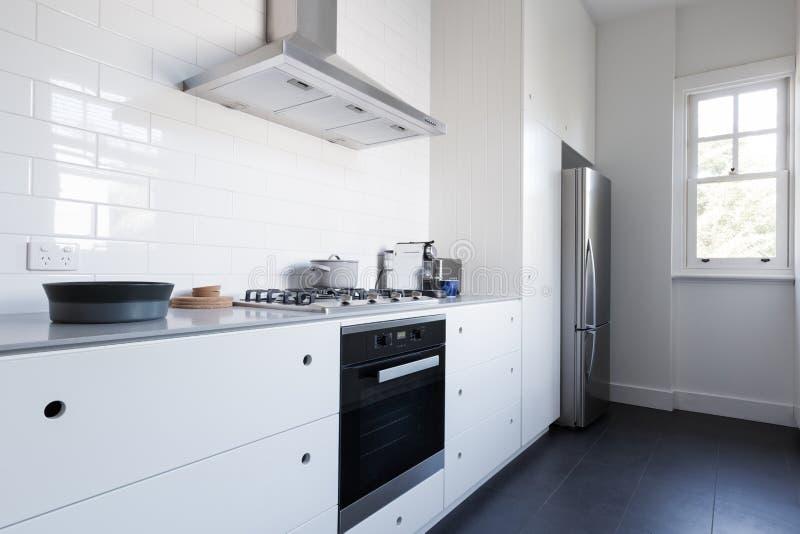 Μονοχρωματική καθαρή άσπρη κουζίνα benchtop με τις συσκευές στοκ εικόνες με δικαίωμα ελεύθερης χρήσης