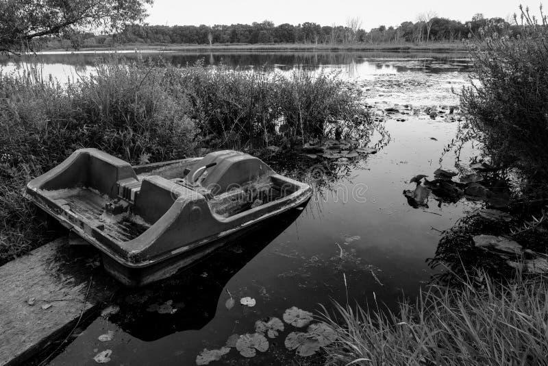 Μονοχρωματική παλαιά σπασμένη βάρκα κουπιών στην πλευρά μιας μικρής λίμνης του Μίτσιγκαν στοκ φωτογραφίες