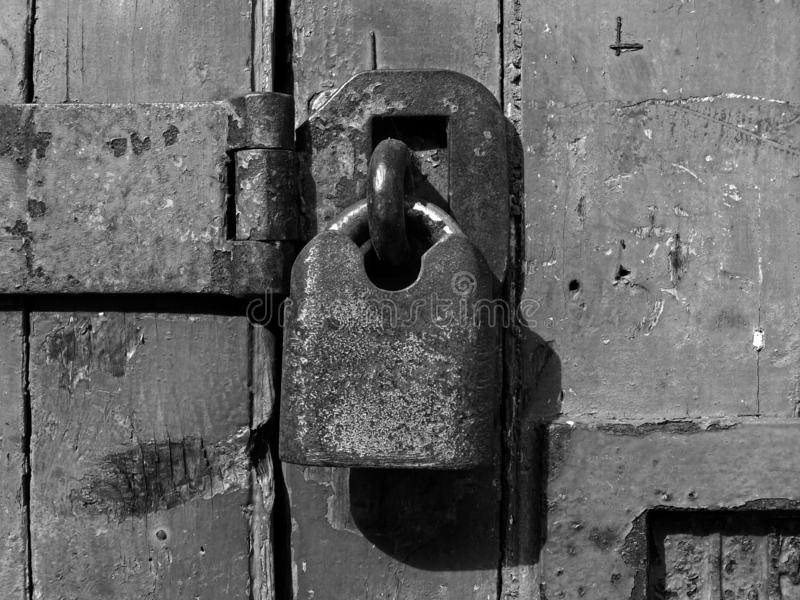 μονοχρωματικός στενός επάνω ενός παλαιού σκουριασμένου κλειστού λουκέτου και hasp σε μια στενοχωρημένη ξύλινη πόρτα σανίδων στοκ φωτογραφίες