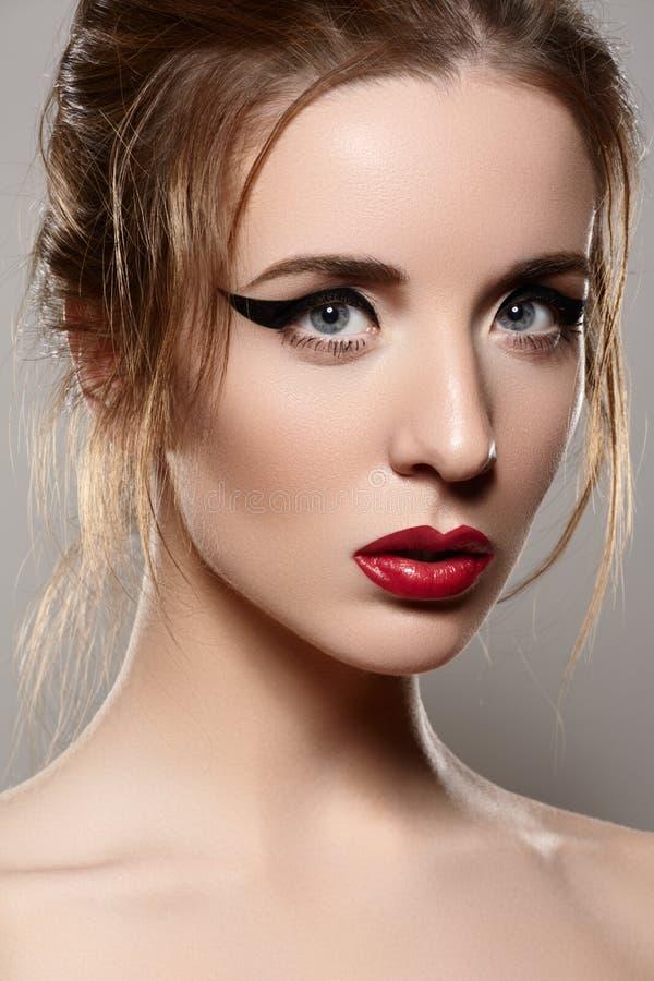 Μοντέλο με την αναδρομική σύνθεση, εκλεκτής ποιότητας κόκκινα χείλια & eyeliner στοκ εικόνα