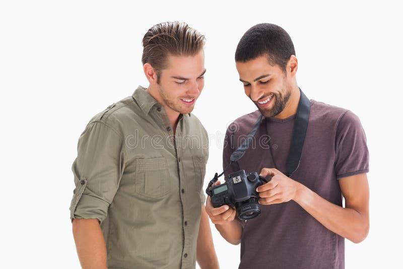 Μοντέρνα άτομα που εξετάζουν τη ψηφιακή κάμερα στοκ φωτογραφίες με δικαίωμα ελεύθερης χρήσης