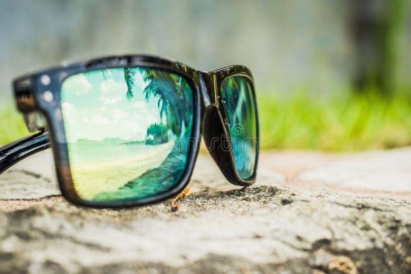 Μοντέρνα γυαλιά ηλίου Γυαλιά ηλίου με τους αντανακλημένους φακούς Αντανάκλαση της παραλίας και των τροπικών φοινίκων στα γυαλιά η στοκ εικόνες