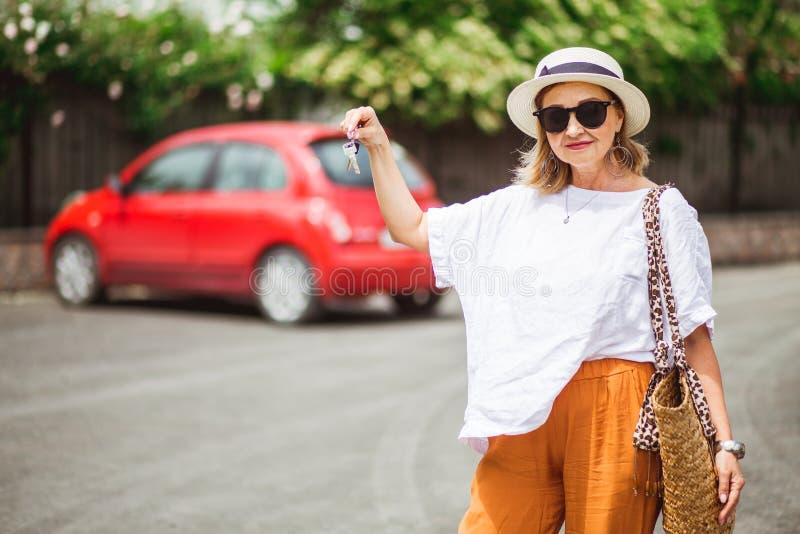 Μοντέρνα, μέσος-γερασμένα κλειδιά εκμετάλλευσης γυναικών για το νέο κόκκινο αυτοκίνητο και χαμόγελο στη κάμερα Έτοιμος για το ταξ στοκ εικόνες