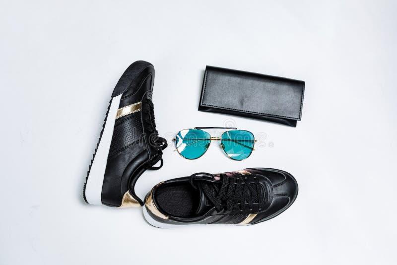 Μοντέρνα πάνινα παπούτσια σε ένα άσπρο πέλμα με τις μαύρες κάλτσες και τις χρυσές εμφάσεις, γυαλιά ηλίου με τα μπλε γυαλιά και έν στοκ εικόνες