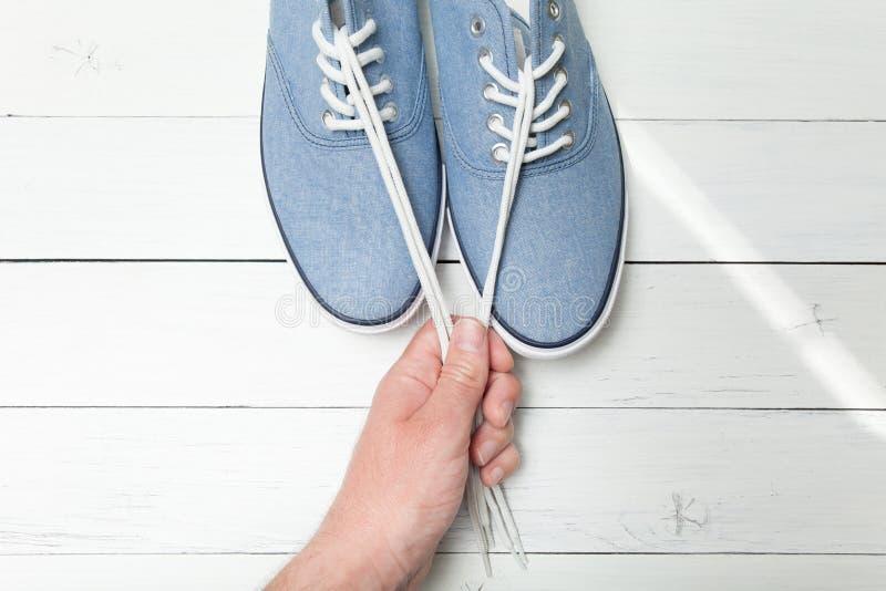 Μοντέρνα παπούτσια σε ένα ελαφρύ ξύλινο υπόβαθρο, άσπρες δαντέλλες σε ένα χέρι στοκ εικόνα