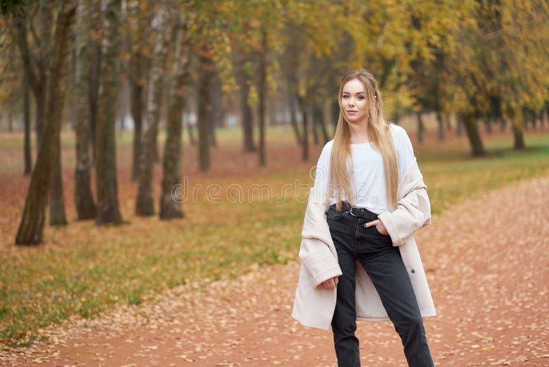 Μοντέρνα συλλογή δρόμων Νεαρή ξανθιά κοπέλα με αυτοπεποίθηση που φοράει λευκό πουκάμισο, μαύρο τζιν, μοδάτο φθινοπωρινό παλτό και στοκ φωτογραφία