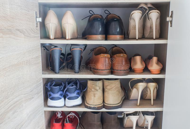 Μοντέρνα υψηλά τακούνια γυναικών, παπούτσια ανδρών δέρματος και αθλητικά παπούτσια στο ξύλινο γραφείο για τη μετάβαση να εργαστεί στοκ φωτογραφία με δικαίωμα ελεύθερης χρήσης