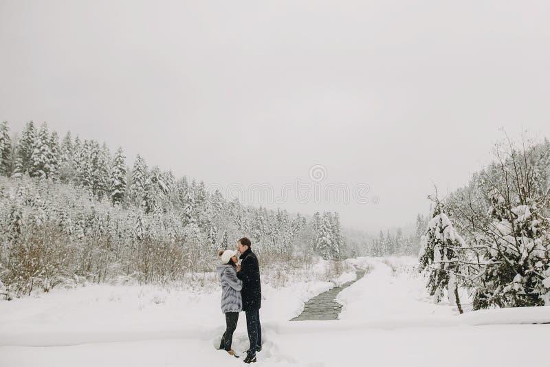 Μοντέρνα χέρια εκμετάλλευσης ζευγών ερωτευμένα και αγκάλιασμα στο χιονώδες moun στοκ εικόνες με δικαίωμα ελεύθερης χρήσης
