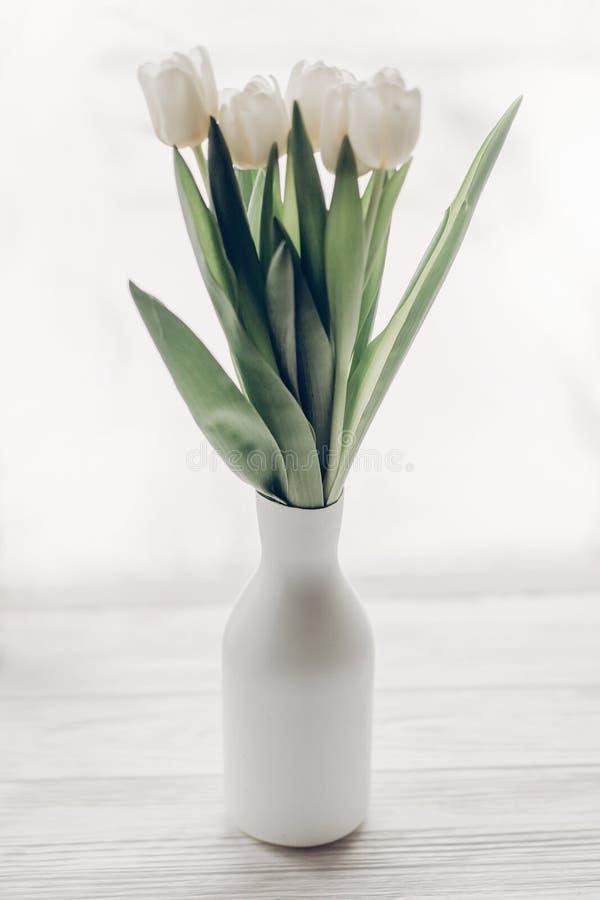 Μοντέρνες άσπρες τουλίπες στο minimalistic μοντέρνο βάζο σε ξύλινο στοκ φωτογραφία με δικαίωμα ελεύθερης χρήσης