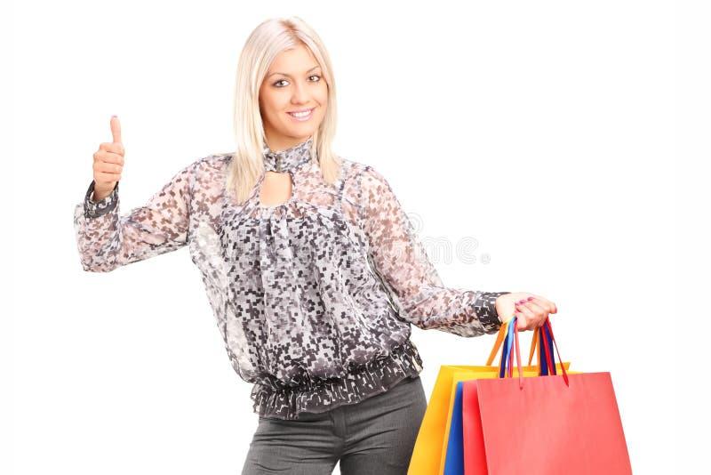 Μοντέρνες τσάντες αγορών εκμετάλλευσης γυναικών και δόσιμο του αντίχειρα επάνω στοκ φωτογραφία με δικαίωμα ελεύθερης χρήσης