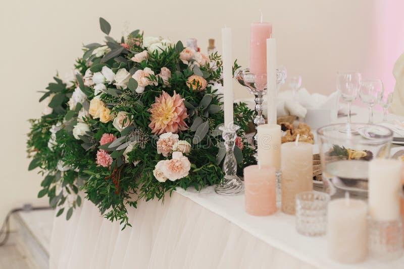 Μοντέρνες όμορφες ανθοδέσμες με τα τριαντάφυλλα και κεριά στην κρητιδογραφία tabl στοκ εικόνες