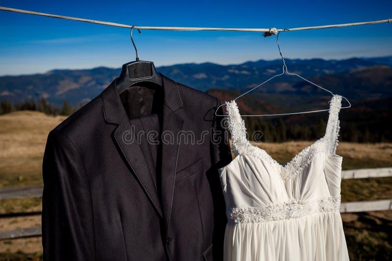 Μοντέρνη ένωση γαμήλιων φορεμάτων και κοστουμιών στην κρεμάστρα Καταπληκτικό υπόβαθρο τοπίων βουνών στοκ φωτογραφία με δικαίωμα ελεύθερης χρήσης