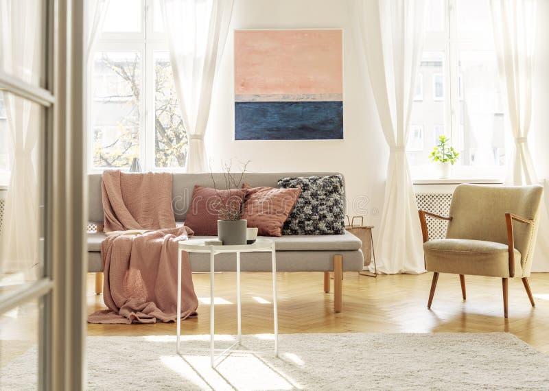 Μοντέρνη αναδρομική καρέκλα δίπλα στον κομψό γκρίζο καναπέ με τα μαξιλάρια και το κάλυμμα στοκ φωτογραφία με δικαίωμα ελεύθερης χρήσης