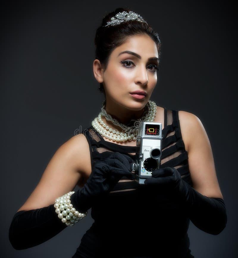 Μοντέρνη αναδρομική νέα γυναίκα με τη φωτογραφική μηχανή κινηματογράφων στοκ φωτογραφία με δικαίωμα ελεύθερης χρήσης