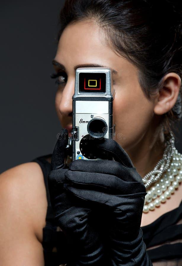 Μοντέρνη αναδρομική νέα γυναίκα με τη φωτογραφική μηχανή κινηματογράφων στοκ εικόνα