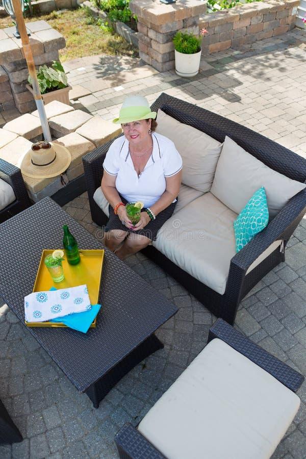 Μοντέρνη ανώτερη κατανάλωση γυναικών σε ένα patio στοκ εικόνα