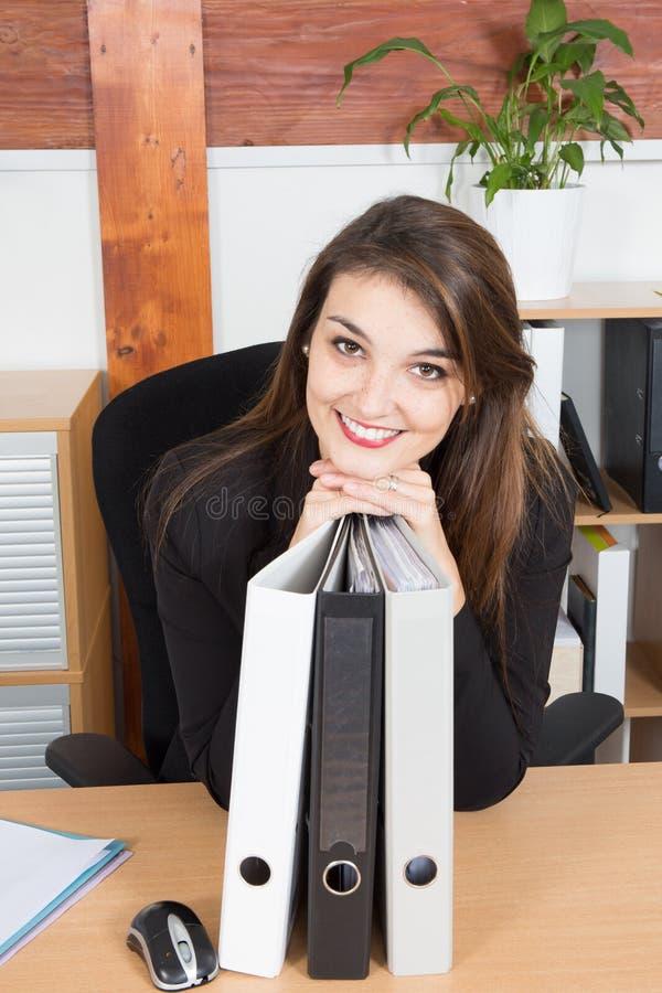 μοντέρνη αρκετά νέα επιχειρηματίας που κλίνει στο φάκελλο στο γραφείο της στο χαμόγελο γραφείων στοκ φωτογραφία με δικαίωμα ελεύθερης χρήσης