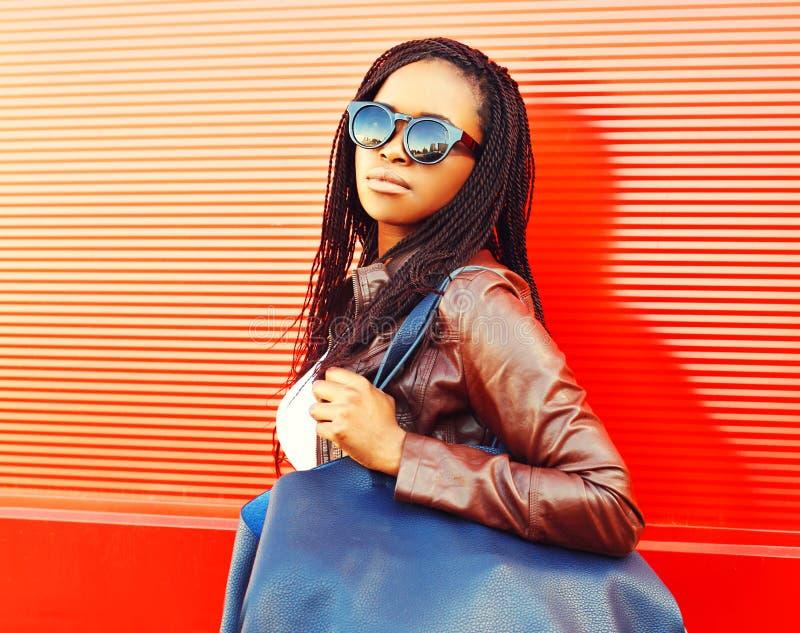 Μοντέρνη αφρικανική γυναίκα στα γυαλιά ηλίου με την τσάντα που περπατά στην πόλη στοκ εικόνες