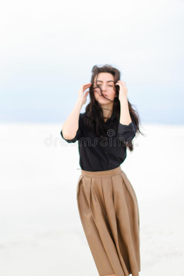 Μοντέρνη γοητευτική γυναίκα που στέκεται στο χειμερινό μονοφωνικό υπόβαθρο και που φορά το μαύρο πουκάμισο με τη φούστα στοκ εικόνες
