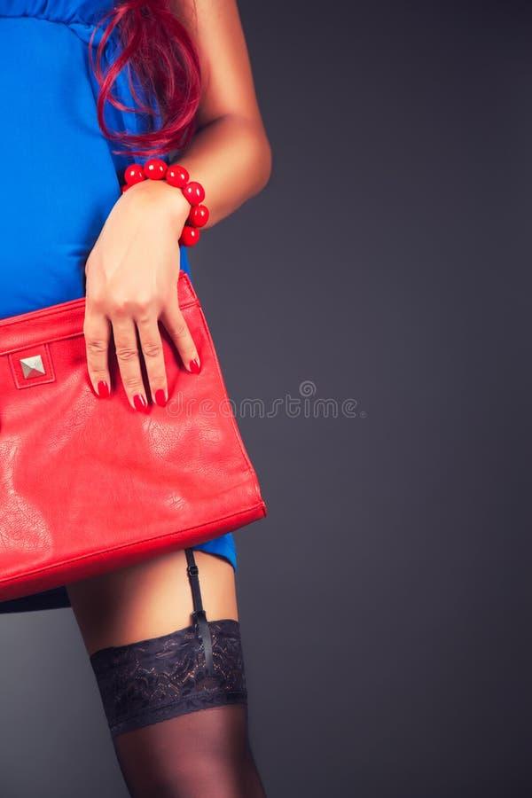 Μοντέρνη γυναίκα με μια κόκκινη τσάντα στοκ εικόνα με δικαίωμα ελεύθερης χρήσης