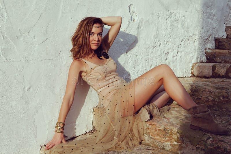 Μοντέρνη μοντέρνη γυναίκα με τα όμορφες jewelries και τη συνεδρίαση τιαρών στα παλαιά σκαλοπάτια - εικόνα στοκ φωτογραφία με δικαίωμα ελεύθερης χρήσης