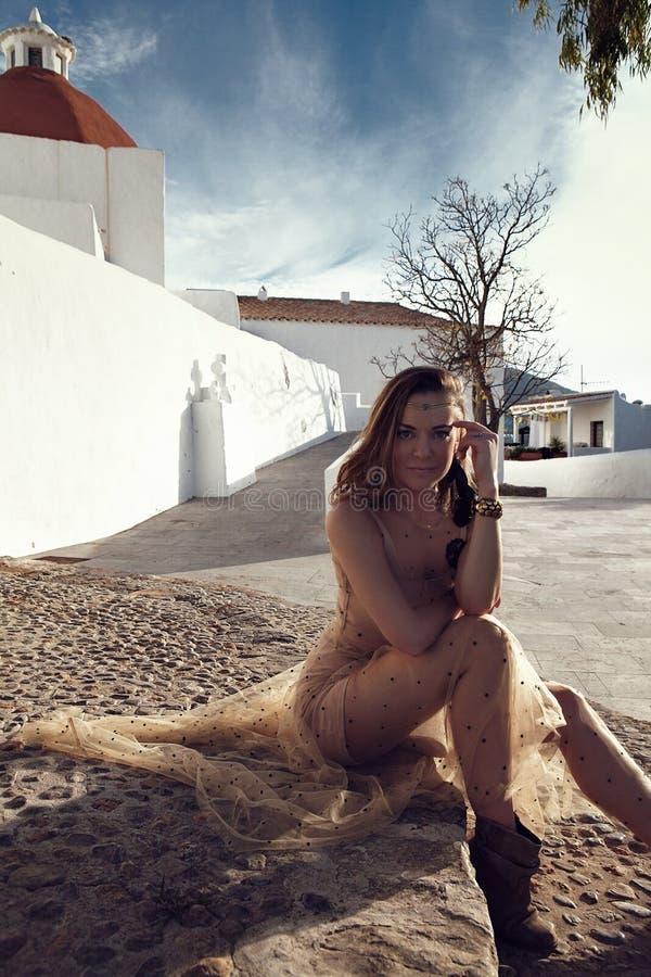 Μοντέρνη μοντέρνη γυναίκα με τα όμορφες jewelries και τη συνεδρίαση τιαρών στα παλαιά σκαλοπάτια πίσω από το παλαιό πόλης λευκό μ στοκ εικόνες με δικαίωμα ελεύθερης χρήσης
