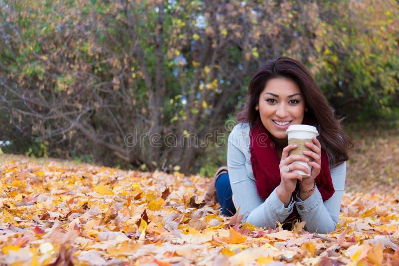 Μοντέρνη γυναίκα με τον καφέ που ξαπλώνει στα φύλλα πτώσης στοκ εικόνα