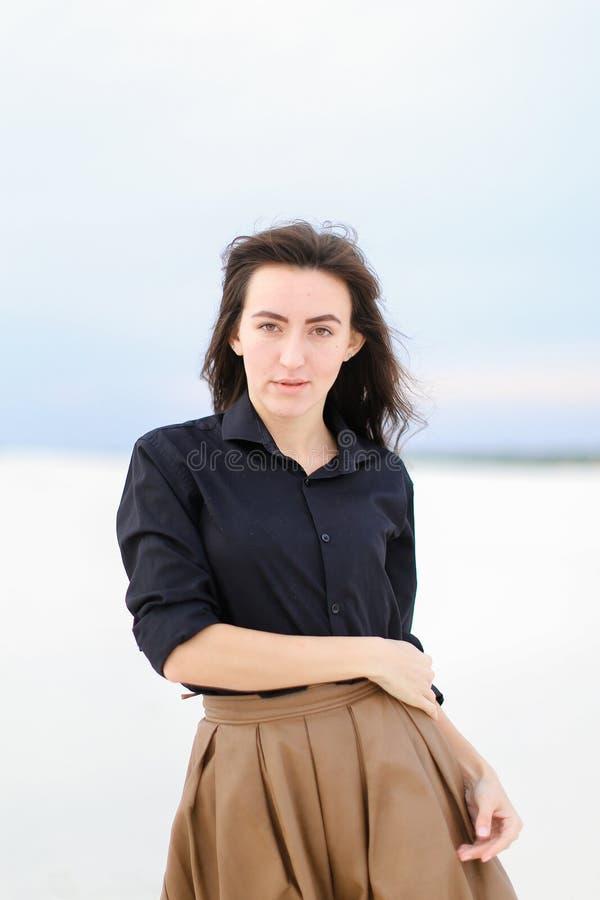 Μοντέρνη γυναίκα που στέκεται στο χειμερινό μονοφωνικό υπόβαθρο και που φορά το μαύρο πουκάμισο με τη φούστα στοκ φωτογραφία με δικαίωμα ελεύθερης χρήσης