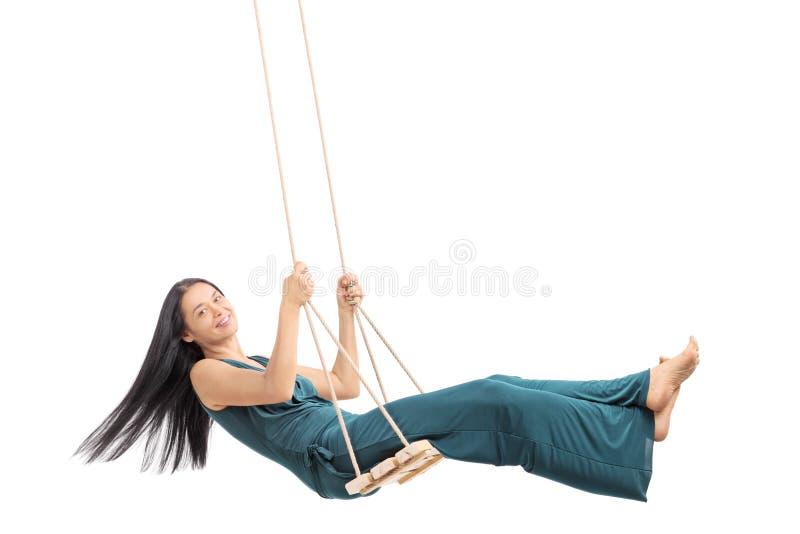 Μοντέρνη γυναίκα που ταλαντεύεται σε μια ξύλινη ταλάντευση στοκ φωτογραφία με δικαίωμα ελεύθερης χρήσης
