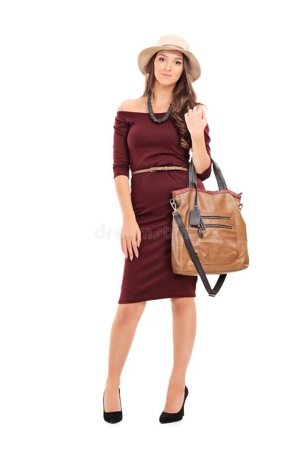 Μοντέρνη γυναίκα που φέρνει μια καθιερώνουσα τη μόδα τσάντα στοκ φωτογραφίες