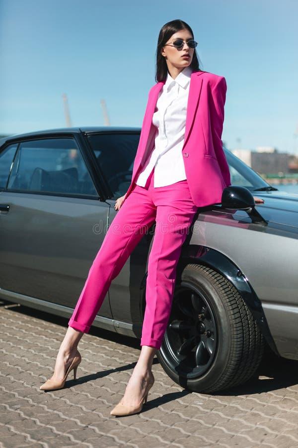 Μοντέρνη γυναίκα σε ένα ρόδινο κοστούμι που περιμένει κοντά στο κλασικό αυτοκίνητο στοκ φωτογραφίες