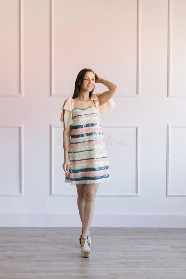 Μοντέρνη γυναίκα σε μια ζωηρόχρωμη τοποθέτηση φορεμάτων λωρίδων σε ένα στούντιο στοκ εικόνα