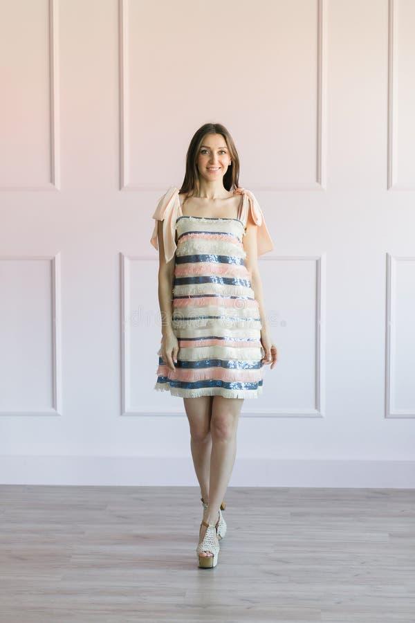 Μοντέρνη γυναίκα σε μια ζωηρόχρωμη τοποθέτηση φορεμάτων λωρίδων σε ένα στούντιο στοκ εικόνες