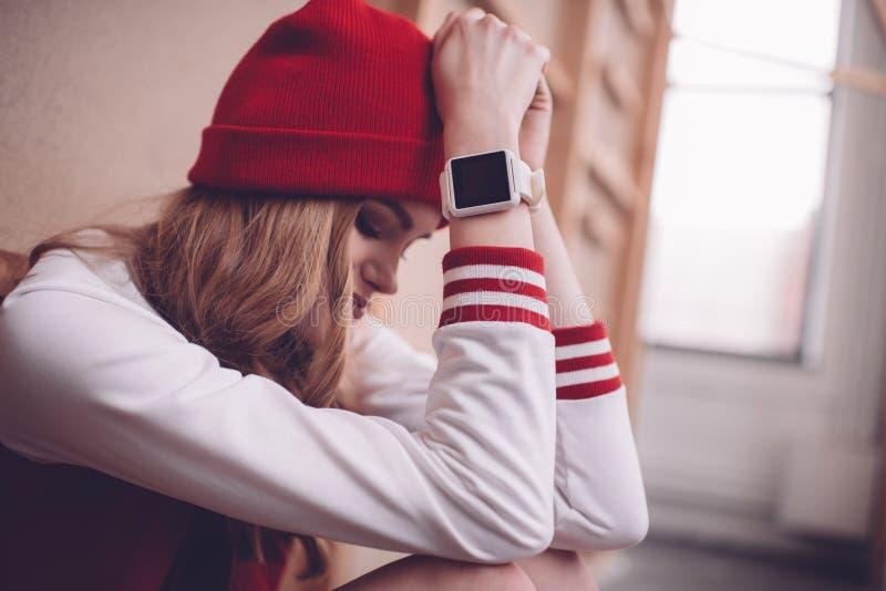 Μοντέρνη γυναίκα hipster με τη συνεδρίαση και το κοίταγμα smartwatch κάτω στοκ φωτογραφία