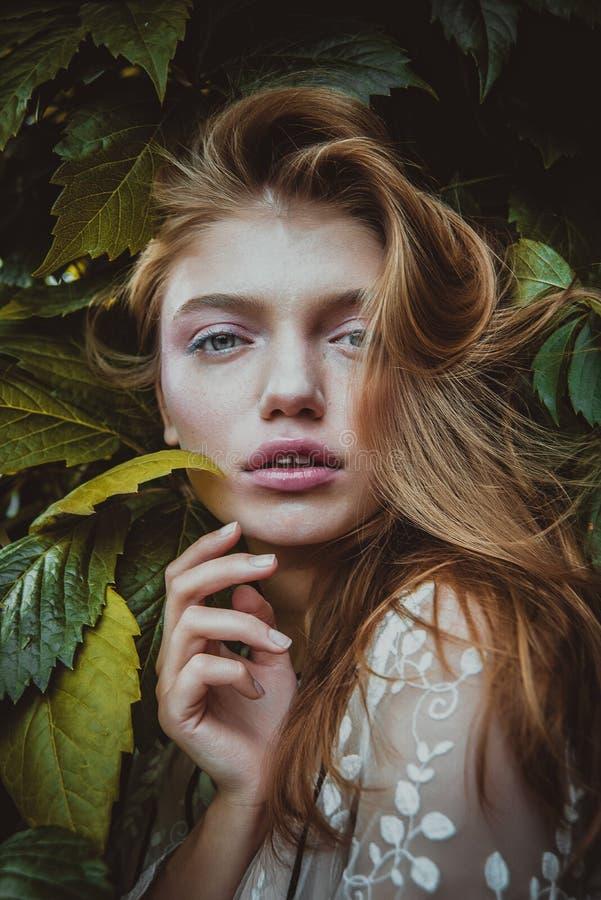 Μοντέρνη γυναίκα hipster με το αγκάλιασμα φύλλων φτερών πορτρέτο κοριτσιών με το φυσικό χορτάρι, αισθησιακή νύφη boho αγαπημένος  στοκ εικόνες