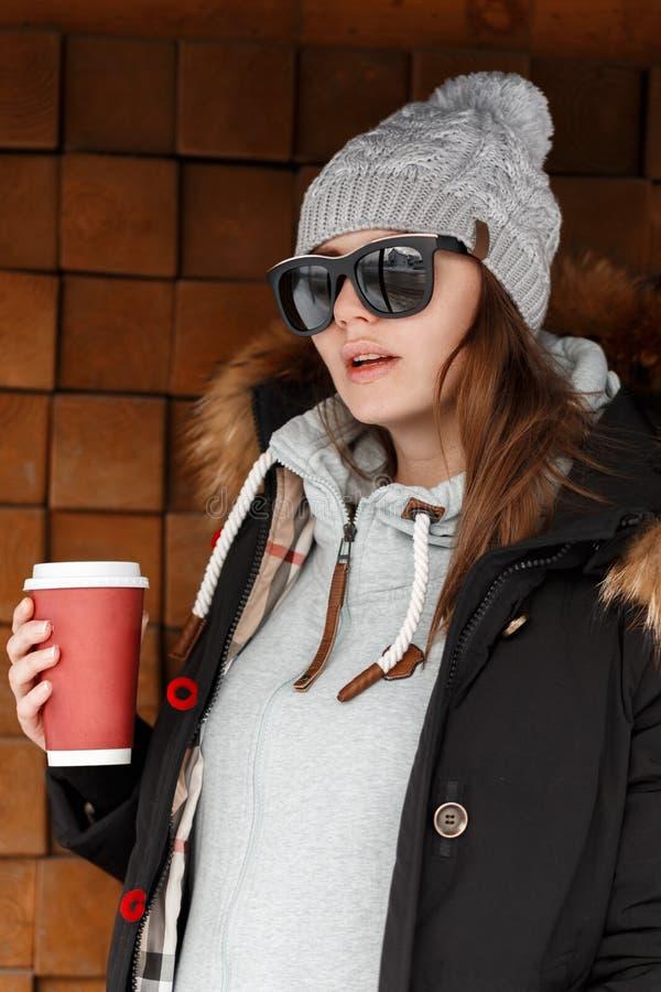 Μοντέρνη ελκυστική νέα γυναίκα hipster στο πλεκτό καπέλο στα γυαλιά ηλίου με ένα μαύρο σακάκι με μια κουκούλα γουνών σε ένα hoodi στοκ εικόνες