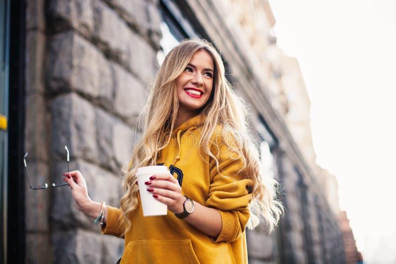 Μοντέρνη ευτυχής νέα γυναίκα που φορά boyfrend τα τζιν, άσπρο φωτεινό κίτρινο sweetshot πάνινων παπουτσιών Κρατά τον καφέ για να  στοκ φωτογραφία