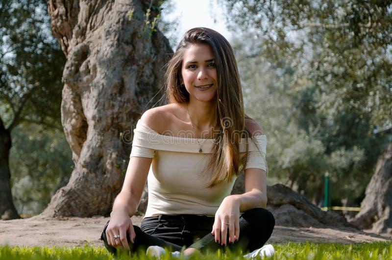Μοντέρνη εύθυμη συνεδρίαση brunette κάτω από ένα δέντρο σε ένα πάρκο στοκ εικόνα